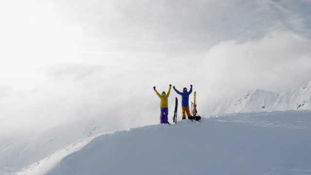 vídeos de stock e filmes b-roll de aerial two backcountry skiers raising their hands on a snowy mountain ridge - casaco de esqui