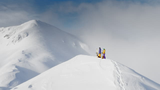 AERIAL Two backcountry skiers standing on a snowy mountain ridge