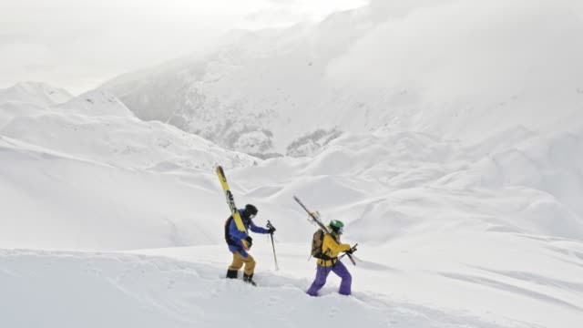 vídeos de stock e filmes b-roll de aerial two backcountry skiers walking across a snowy mountain - casaco de esqui