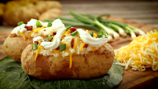Two baked potatoes fully garnished with fixings.