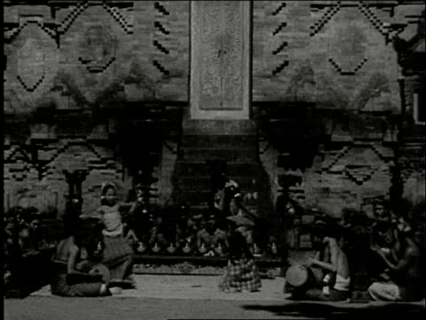 vídeos de stock e filmes b-roll de two balinese temple dancer girls perform elaborate dance in fron of gamelan orchestra / cu girls smiling and laughing bali temple two girls dancing... - gamelão