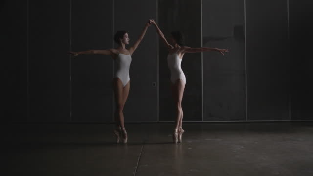 vídeos de stock e filmes b-roll de two ballerinas performing penchã© on point - andar em bico de pés