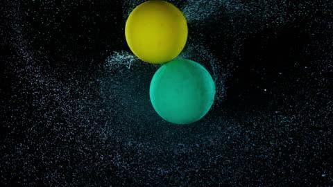 stockvideo's en b-roll-footage met slo mo ld twee ballonnen spuiten water tijdens het draaien in de lucht stoten in elkaar - inslag