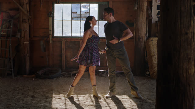 Two ballroom dancers kick up dust while performing their elegant routine in a rustic barn in the Nevada desert.