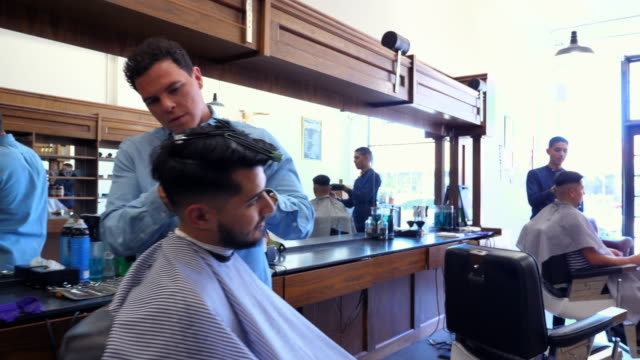 ms zo two barbers working on clients hair in barber shop - barber chair stock videos & royalty-free footage