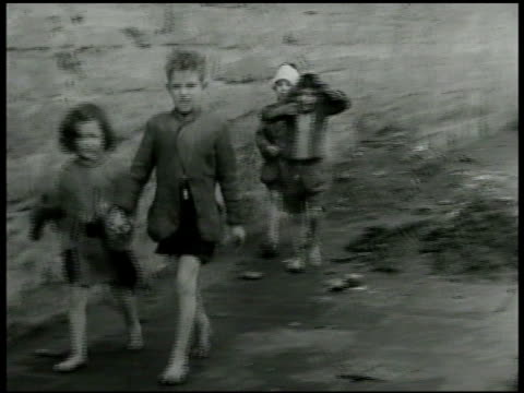 Two barefoot children walking on sidewalk w/ older boy holding hand of of girl two other boys following one w/ head bandaged the other holding coat...