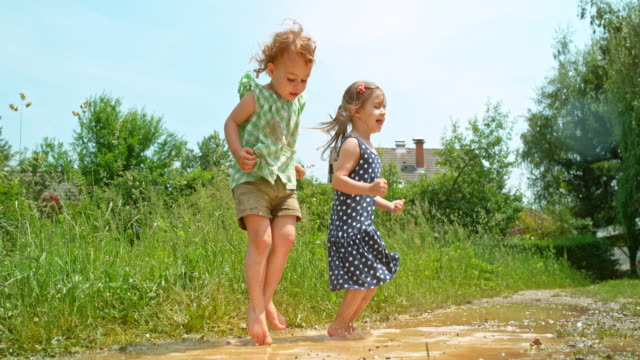 slo mo two barefoot little girls jumping up and down in a muddy puddle in sunshine - mud stock videos & royalty-free footage
