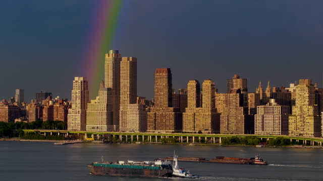 Two barges move along the Hudson River beneath a vibrant rainbow above New York City skyscrapers.