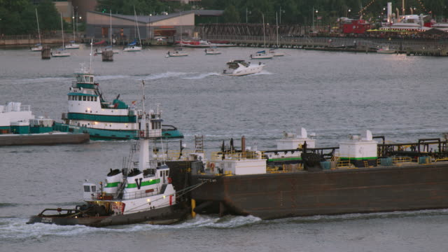 two barges pass each other on the hudson river in new york city. - chiatta video stock e b–roll