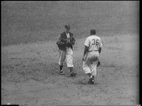 two baseball players walking toward each other + patting each other on sides / nyc - 1951点の映像素材/bロール