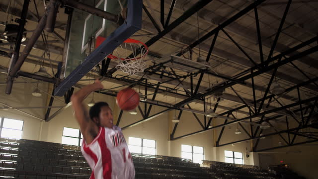 SLO MO. Two basketball players in uniform score an alley-oop in a two-on-two game.