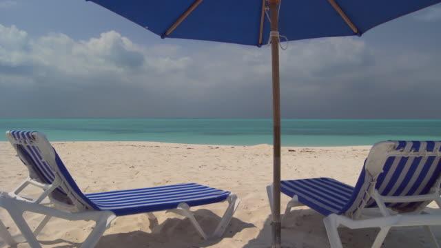 vídeos de stock, filmes e b-roll de ms, two beach chairs under sun umbrella facing ocean, abaco islands, bahamas - espreguiçadeira