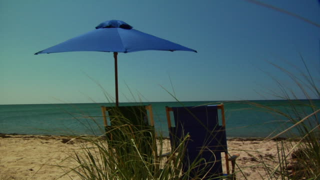 vídeos de stock e filmes b-roll de ms, two beach chairs under sun umbrella facing ocean, north truro, massachusetts, usa - chapéu de sol