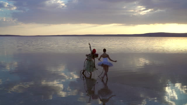Two beautiful dancers on the lake at sunset.