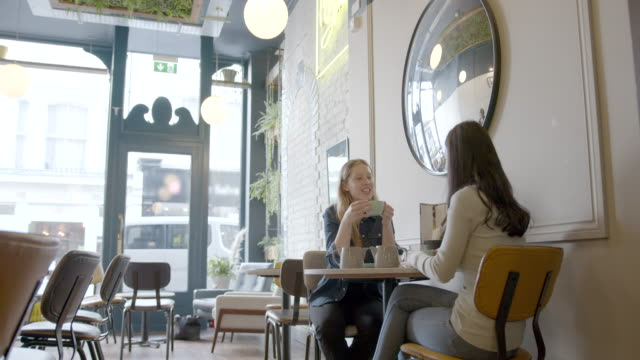 two beautiful female friends meeting in empty cafe restaurant and drinking tea - social distancing stock videos & royalty-free footage