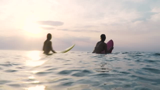 Two beautiful female surfers looking for waves in the Atlantic ocean at sunset in Southern France.