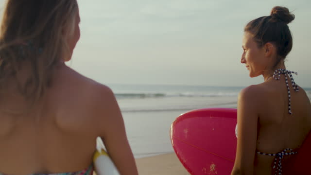 vídeos y material grabado en eventos de stock de two beautiful female surfers looking out at surf on beach with surfboards in bikinis at atlantic coast in south of france. - tabla de surf