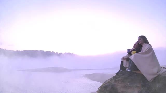 two beautiful friends drinking tea near beautiful foggy lake. - blanket stock videos & royalty-free footage