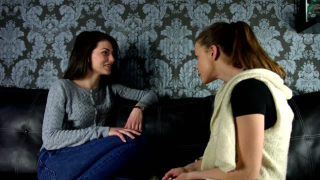 Deux belles copines parler des commérages de rire et de s'amuser sur le canapé