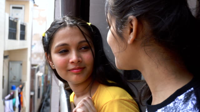 two beautiful girls gossiping in balcony - standing stock videos & royalty-free footage
