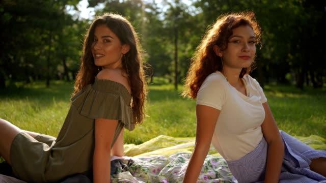 vidéos et rushes de deux belles filles s'asseyant sur l'herbe - jeune d'esprit