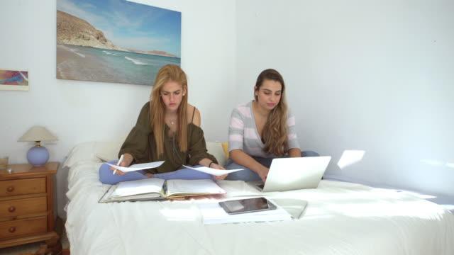 vídeos y material grabado en eventos de stock de two beautiful girls studying in a bright bedroom with notes and laptop - encuadre de tres cuartos