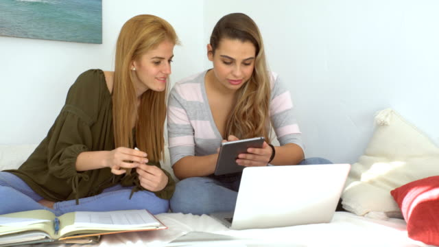 Two beautiful girls studying in a bright bedroom with notes and laptop