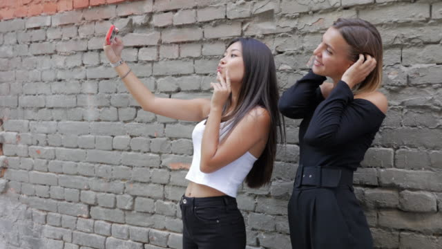 two beautiful girls use a smartphone for selfie - muro video stock e b–roll