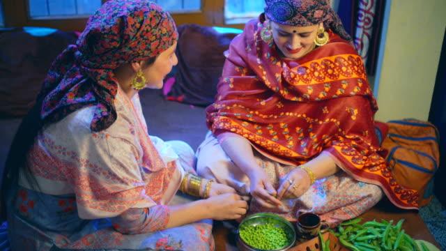 vidéos et rushes de deux belles femmes himachali potins, peaux de peas et boire du thé à la maison. - châle