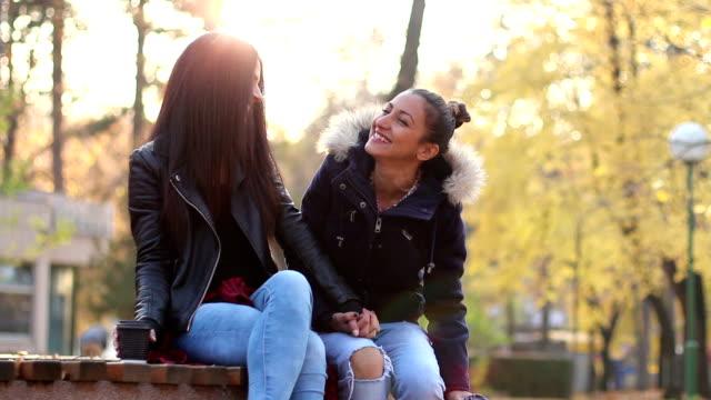 zwei schöne lesbische mädchen trinken kaffee, reden und lachen im park. sie sitzen auf einer bank im park und hände halten, mit herbst bäumen im hintergrund. - 2 lesben stock-videos und b-roll-filmmaterial