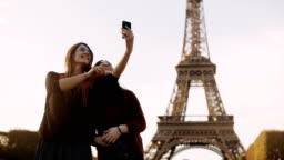 Two beautiful traveling female taking photos on smartphone near the Eiffel tower in Paris, France in sunny day