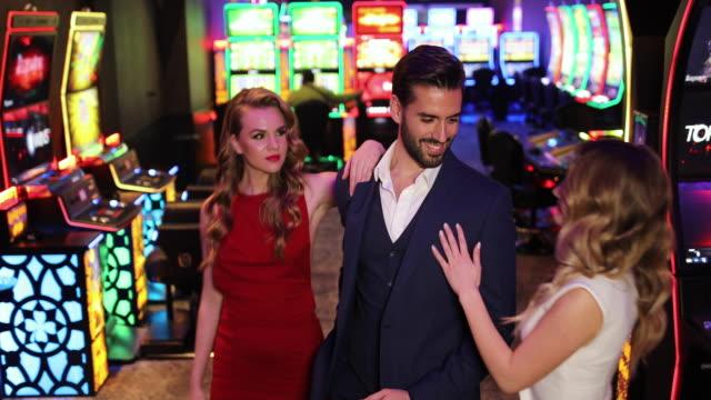 vídeos y material grabado en eventos de stock de dos hermosas mujeres y apuesto hombre de negocios de pie en el casino y mirándose el uno al otro - vestido