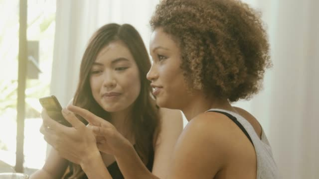 two beautiful women at breakfast table using smart phone - surfing the net stock videos & royalty-free footage