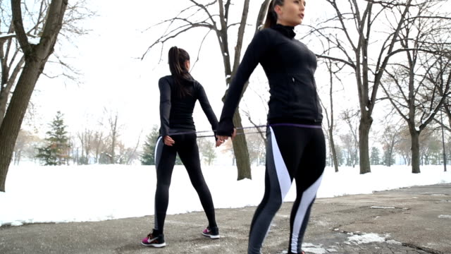 two beautiful women exercising with rubber band - matching outfits stock videos & royalty-free footage