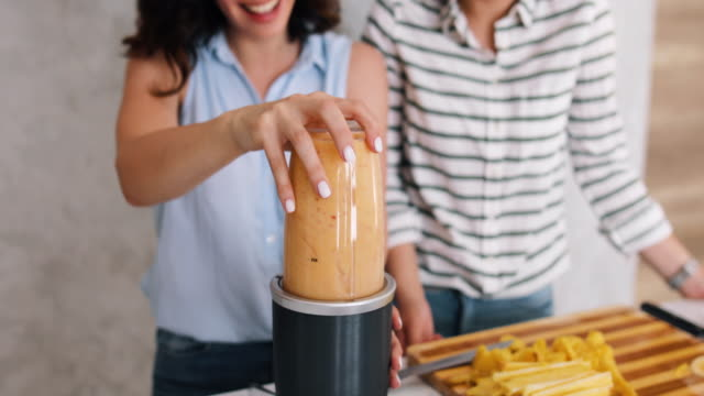 two beautiful women in their kitchen preparing banana and pineapple smoothies. young women mix the ingredients, drink smoothies from a glass jar. healthy way, diet, weight loss concept - smoothie stock videos & royalty-free footage