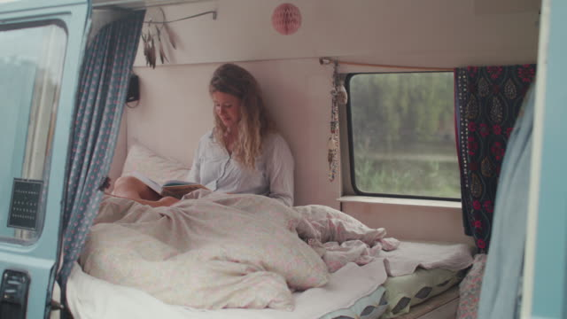 Two beautiful women reading in bed in a van/camping