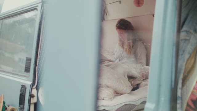 two beautiful women reading in bed in a van/camping - furgone video stock e b–roll