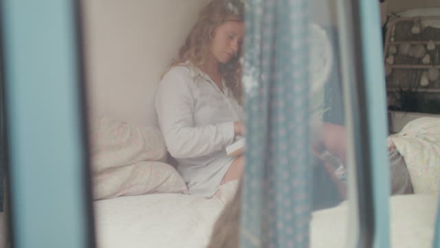 two beautiful women reading in bed in a van/camping - morbidezza video stock e b–roll