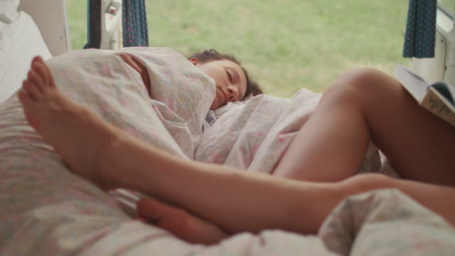 two beautiful women reading/sleeping in bed in a van/camping - furgone video stock e b–roll