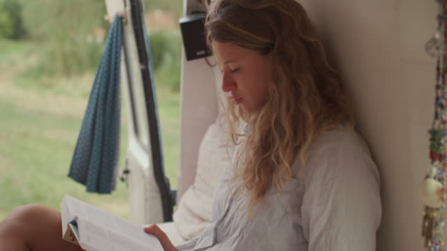 two beautiful women reading/sleeping in bed in a van/camping - summer reading stock videos & royalty-free footage