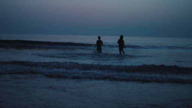 two beautiful women running into ocean, diving into wave at dusk at atlantic coast in france. - date night romance stock videos and b-roll footage