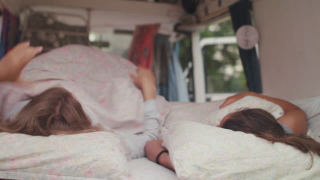 two beautiful women waking up in bed in a van/camping - van stock videos & royalty-free footage