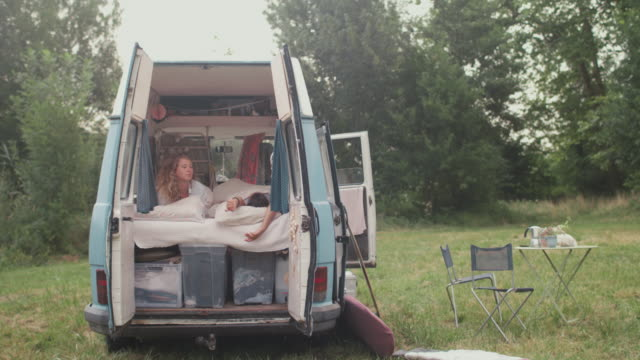 two beautiful women waking up in bed in a van/camping - van vehicle stock videos and b-roll footage