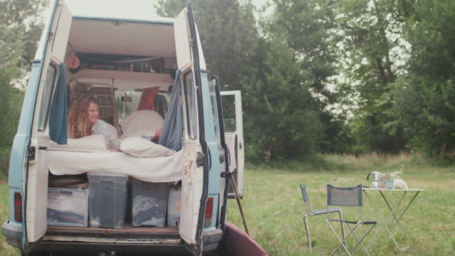 two beautiful women waking up in bed in a van/camping - aquitaine stock-videos und b-roll-filmmaterial