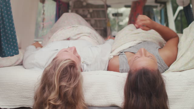 two beautiful women waking up in bed in a van/camping - bed stock videos & royalty-free footage