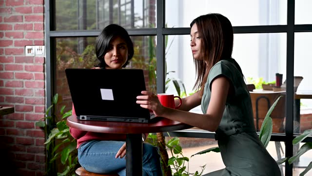 two beautiful young co-workers looking at laptop and talking about business strategy at office - mixed race person stock videos & royalty-free footage