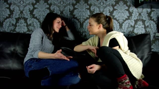 Deux belles jeunes filles parler bavarder et rire sur le canapé