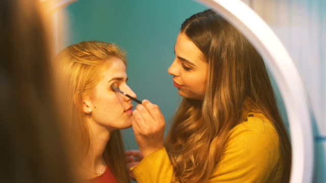 vidéos et rushes de two beautiful young women enjoying and laughing while they are in make-up in front of the mirror - quête de beauté
