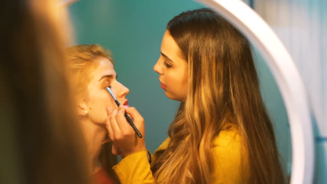 two beautiful young women enjoying and laughing while they are in make-up in front of the mirror - self improvement stock videos & royalty-free footage