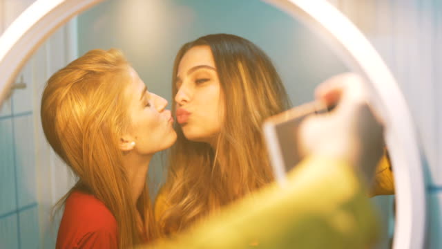 two beautiful young women enjoying and laughing while they take make selfie and they kiss in front of the mirror - lipstick kiss stock videos and b-roll footage